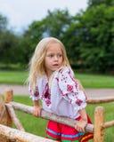 Kleines Mädchen in der ukrainischen Kleidung auf der Hecke Lizenzfreies Stockbild