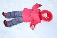 Kleines Mädchen in der warmen Kleidung liegt im Schnee Stockbild
