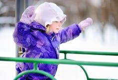 Kleines Mädchen in der Winterkleidung, die Spaß auf Spielplatz am Tag des verschneiten Winters hat Lizenzfreies Stockfoto