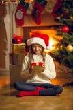 Kleines Mädchen in der Wollstrickjacke, die Weihnachtsgeschenkbox hält stockbilder