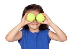 Kleines Mädchen des Brunette mit zwei Tenniskugeln Stockfoto