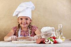 Kleines Mädchen des glücklichen Chefs, das den Teig ausdehnt stockbilder