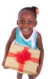 Kleines Mädchen des jungen Afroamerikaners, das eine Geschenkbox hält Stockfotos