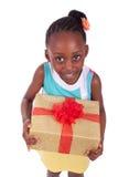 Kleines Mädchen des jungen Afroamerikaners, das eine Geschenkbox hält Stockbild