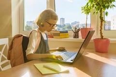 Kleines Mädchen des jungen Hackers in den Gläsern mit einem Schulrucksack, der am Computer, Laptop arbeitet lizenzfreie stockbilder