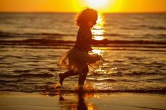 Kleines Mädchen des kleinen Mädchens in einem Rock und in einer gestreiften Strickjacke lässt thro laufen Stockfoto
