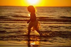 Kleines Mädchen des kleinen Mädchens in einem Rock und in einer gestreiften Strickjacke lässt thro laufen Lizenzfreie Stockfotos