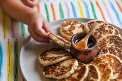 Kleines Mädchen des Morgenfrühstücks zieht eine Hand zu einer Platte mit chee lizenzfreie stockbilder