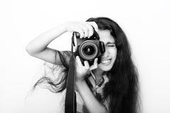 Kleines Mädchen des netten Brunette, das eine Fotokamera hält Stockfotografie