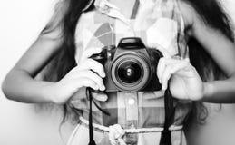 Kleines Mädchen des netten Brunette, das eine Fotokamera hält Lizenzfreie Stockfotos