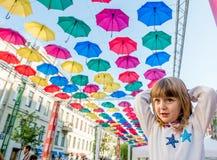 Kleines Mädchen des Porträts in der Straße verziert mit farbigen Regenschirmen Lizenzfreies Stockfoto