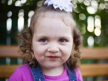Kleines Mädchen des Porträts mit einem weißen Bogen auf ihrem Hauptlächeln schüchtern an der Kamera lizenzfreies stockfoto