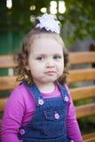 Kleines Mädchen des Porträts mit einem weißen Bogen auf ihrem Hauptlächeln schüchtern an der Kamera lizenzfreies stockbild