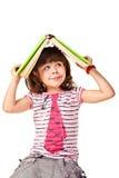 Kleines Mädchen des Taubenschlags mit einem Buch, das oben schaut Stockfoto