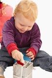 Kleines Mädchen des Ute, das mit Weihnachtsgeschenken spielt Stockbilder