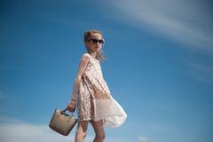 Kleines Mädchen des Zaubers im modischen Kleid und in der Sonnenbrille geht auf den Hintergrund des blauen Himmels, der eine Hand Stockfotografie