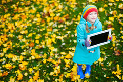 Kleines Mädchen draußen am Herbsttag Stockfotografie