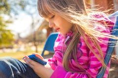 Kleines Mädchen draußen mit Smartphone stockbild