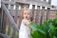 Kleines Mädchen drehte sich herum am Tor und starrt mit offenem Mund an lizenzfreie stockfotos