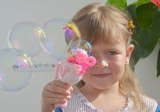 Kleines Mädchen-durchbrennenluftblasen stockfoto