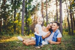 Kleines Mädchen ein Jahr auf dem Hintergrund von den Eltern, die liegend auf dem Gras lernt, auf Natur im Park zu gehen stillsteh Stockfotografie