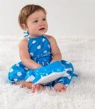 Kleines Mädchen in einem blauen Kleid sitzt auf dem Bett und schaut zur Seite, die mit einem Spielzeug spielt Lizenzfreies Stockfoto