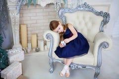 Kleines Mädchen in einem eleganten Kleid, das auf einem Stuhl sitzt und ohne den Rahmen zu betrachten Lizenzfreies Stockbild