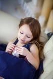 Kleines Mädchen in einem eleganten Kleid, das auf einem Stuhl sitzt und ohne den Rahmen zu betrachten Lizenzfreies Stockfoto