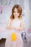 Kleines Mädchen in einem eleganten Kleid verzieren den Weihnachtsbaum Stockfoto