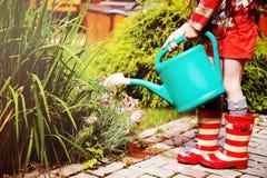 Kleines Mädchen in einem Garten mit grüner Bewässerungsdose Lizenzfreie Stockbilder