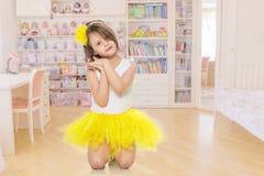 Kleines Mädchen in einem gelben Rock und in einem weißen T-Shirt Stockbilder