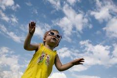 Kleines Mädchen in einem gelben T-Shirt mit der Sonnenbrille, die auf Hintergrund des blauen Himmels springt Horizontale Abbildun Stockfoto