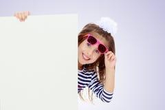 Kleines Mädchen in einem gestreiften Kleid Stockbilder