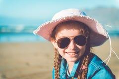 Kleines Mädchen in einem Hut auf dem Strand Stockfotos
