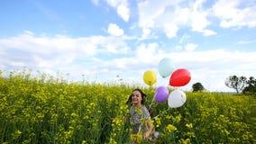 Kleines Mädchen in einem Kleid, das in der Hand durch gelbes Weizenfeld mit Ballonen läuft Zeitlupen stock video footage
