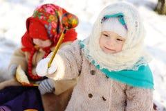 Kleines Mädchen in einem Kopftuch in der russischen Art, mit einem hölzernen s lizenzfreies stockbild