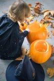 Kleines Mädchen in einem Kostüm einer Hexe, die nahe zwei Kürbisen sitzt Lizenzfreie Stockfotografie
