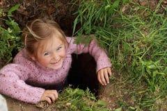 Kleines Mädchen in einem Loch Stockfotos