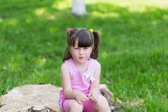 Kleines Mädchen in einem Park auf einem Stumpf lizenzfreie stockfotos