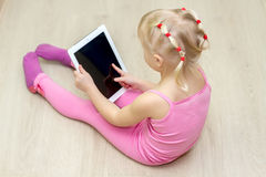 Kleines Mädchen in einem rosa Kleid bedrängt einen Tablettenschirm stockbilder