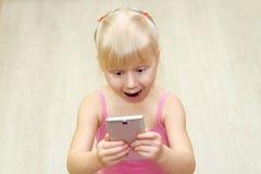 Kleines Mädchen in einem rosa Kleid erschrak mit Handy lizenzfreie stockfotos
