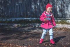 Kleines Mädchen in einem rosa Mantel, in den Jeans und in den Stiefeln gehend der Park stockfotografie