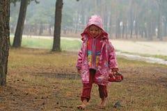 Kleines Mädchen in einem rosa Regenmantel Stockbild