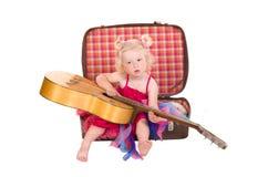 Kleines Mädchen in einem rosafarbenen Kleid, das Gitarre spielt lizenzfreies stockbild