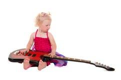 Kleines Mädchen in einem rosafarbenen Kleid, das Gitarre spielt lizenzfreie stockbilder