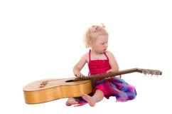 Kleines Mädchen in einem rosafarbenen Kleid, das Gitarre spielt lizenzfreies stockfoto