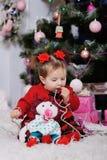 Kleines Mädchen in einem roten Kleid auf Hintergrund des Weihnachtsbaums stockbild