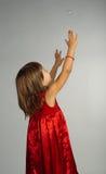 Kleines Mädchen in einem roten Kleid mit den Händen oben Stockbilder