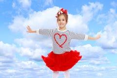 Kleines Mädchen in einem roten Rock und Bogen auf ihrem Kopf Stockbild