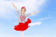 Kleines Mädchen in einem roten Rock und Bogen auf ihrem Kopf Lizenzfreie Stockbilder